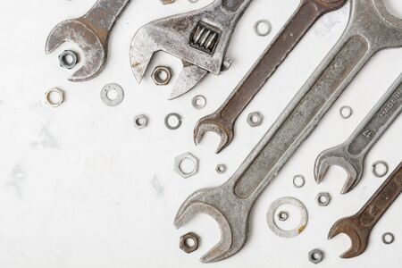 fasteners: A lot of old wrenchs on a light stone background. Nuts and washers of different sizes.