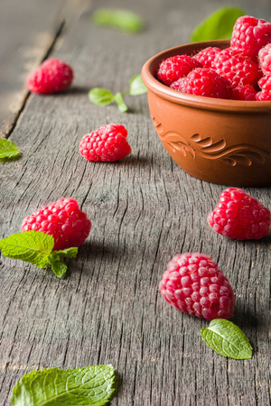 Ripe juicy raspberries on a dark background. Fresh green mint leaves. View from above. Stock Photo