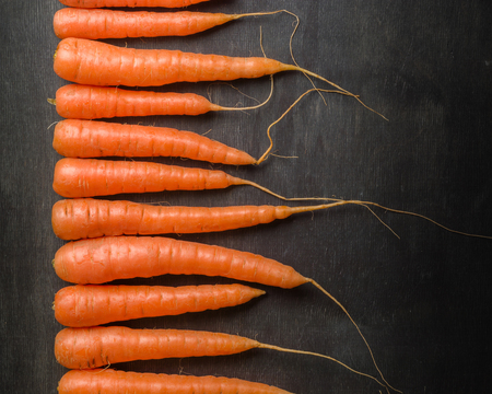 Carrots of various sizes lined up in a row on a black wooden background. Washed and ready to eat. Stock Photo