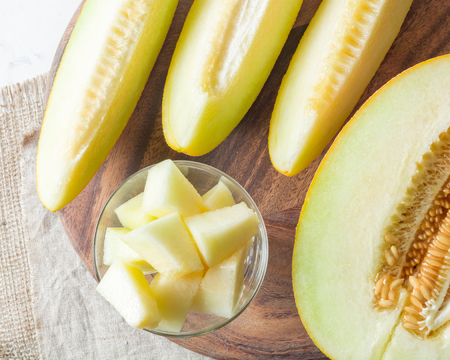 Ripe big and yellow melon. Cut into pieces. Appetizing background. Healthy food.