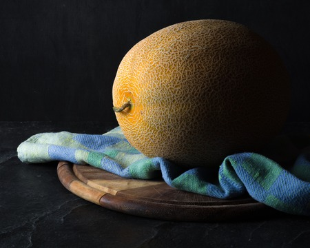 Ripe yellow melon on a dark background. Low key.