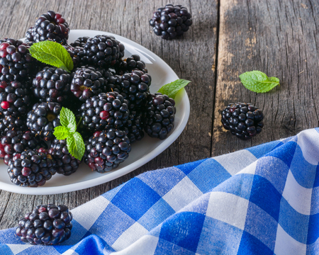 A bunch of blackberries on a white saucer. Gray wooden background. Blue checkered napkin.