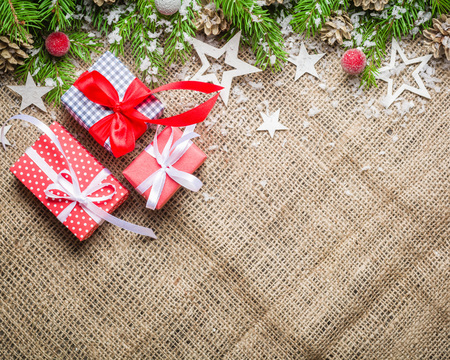 New Year and Christmas background on an old background of sackcloth. View from above. Christmas tree branches and snow, gifts and decorations