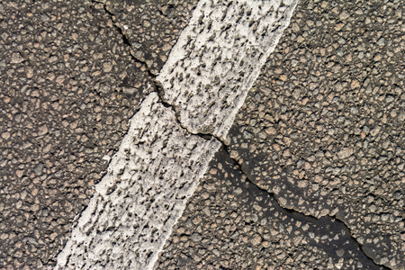 tire tracks: The old cracked asphalt road. White markings on the road. Repair is required. Copy space.