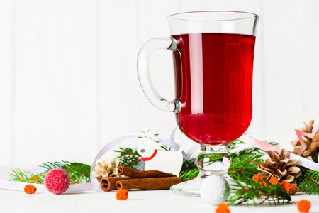 A glass of red hot mulled wine on a light background. Christmas and New Year greeting card. Copy space.