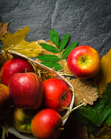 Autumn dark background or frame of fallen yellow leaves and ripe red apples. Frame for text or photo. Applicable for an article about autumn or crop. Copy space.