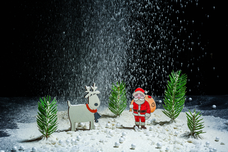 New Years background. Figures of Santa Claus, deer and boy. Snow angel. Snowing. Night frame. Billet for postcards or congratulations. Copy space Stock Photo