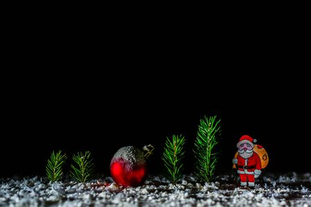 Night and dark New Years background. Billet for postcards or congratulations. In the forest among the snowdrifts. Firs and figurines of Santa Claus and deer. Stock Photo