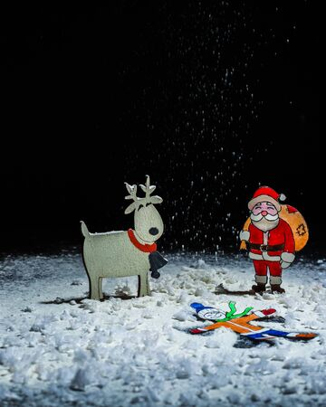 Paper figures of the child as a snow angel Santa Claus and deer. Hand made paper figurine. A blank for a postcard. Copy space.