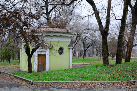 An old circular building in an autumn park. A gloomy day and loneliness.