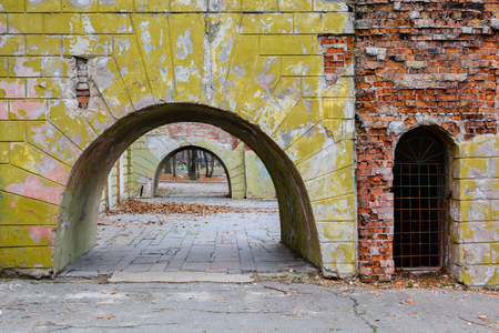 Huge arches in an old brick wall with remnants of plaster