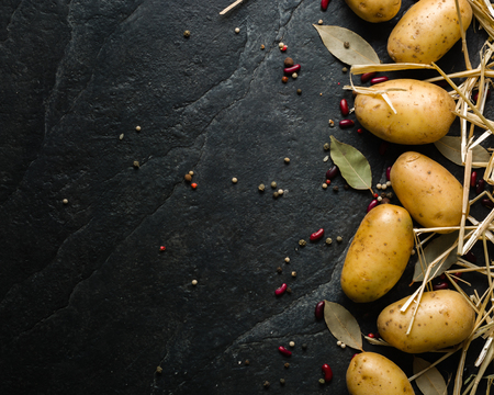 A pile of raw potatoes on a dark stone background. Preparation of soup or potato dishes.