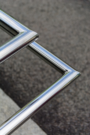 Polished stainless pipes welded at an angle. Gray industrial background.
