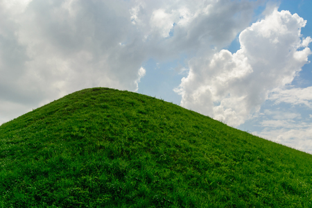 Summer background. warm sunny weather on a green grass hill. A blue sky with white clouds. Фото со стока