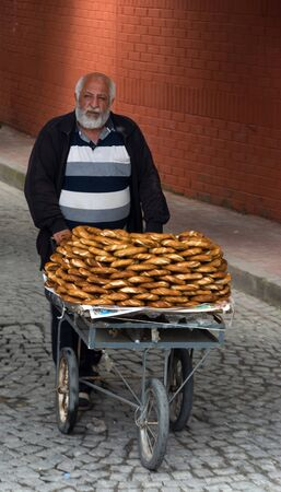 ISTANBUL-MAY 20: A old man sells sesame bagels on a cart May 20, 2015 Istanbul, Turkey Sajtókép