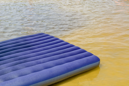 Blue inflatable mattress on the summer shore of the river or lake. Recreation and entertainment near the water in nature. Reklamní fotografie
