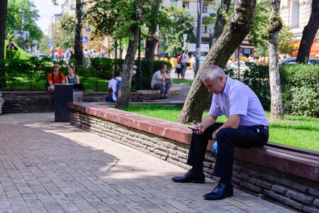 KIEV, UKRAINE - 20 JUNE 2018: man texting with his mobile phone, he is sitting on a wooden bench Sajtókép