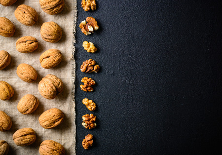 Walnuts on a black slate. Whole and peeled nuts. Walnuts spread out evenly. Copy space. Standard-Bild
