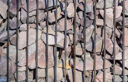 Gabione aus senkrechten Metallstäben und Schotter aus Granit. Industrie- oder Bauhintergrund