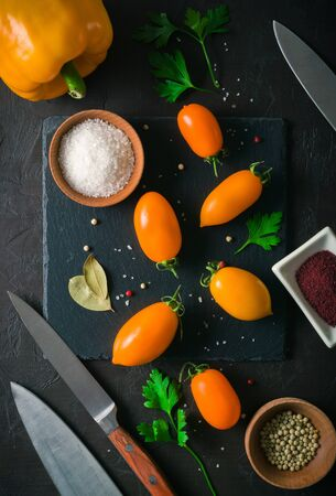 Fresh and juicy orange tomatoes laid out on a dark stone background. View from above. Place for text