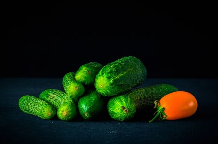 A bunch of fresh green cucumbers lying on a dark table. Side view. Plenty of room for text
