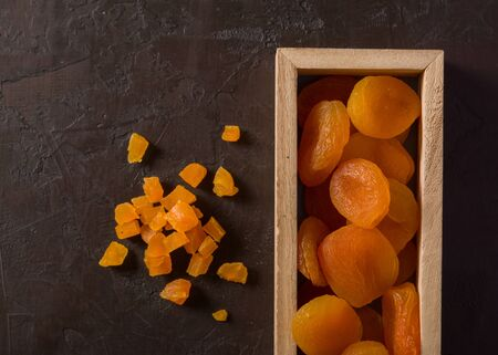 Delicious and healthy dried apricots. Freshly dried. On a brown background in wooden box Reklamní fotografie
