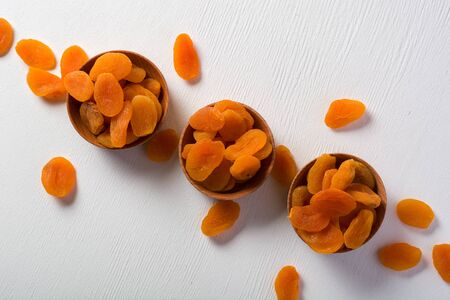 Delicious and healthy dried apricots. Freshly dried. On a white background in wooden bowls