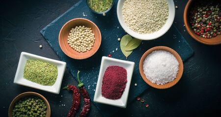 A lot of spices and seasonings in drinking bowls on a dark table. View from above Reklamní fotografie