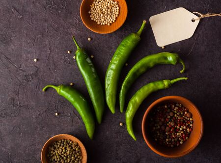 A few green hot peppers shot from above on a dark stone background. Plenty of space for text Stok Fotoğraf - 130136817