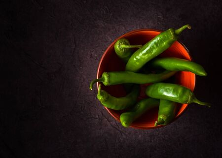 A few green hot peppers shot from above on a dark stone background. Plenty of space for text