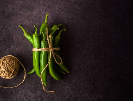 A few green hot peppers shot from above on a dark stone background. Plenty of space for text Stok Fotoğraf - 130136818