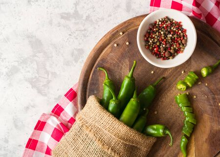 A few green hot peppers in a pouch shot from above on a light stone background and cutting board. Plenty of space for text Stockfoto
