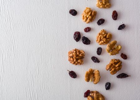 A variety of peeled walnuts and raisins on a white wooden background. View from above. Plenty of space for text Фото со стока - 130136824