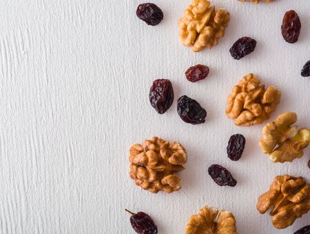 A variety of peeled walnuts and raisins on a white wooden background. View from above. Plenty of space for text Stockfoto