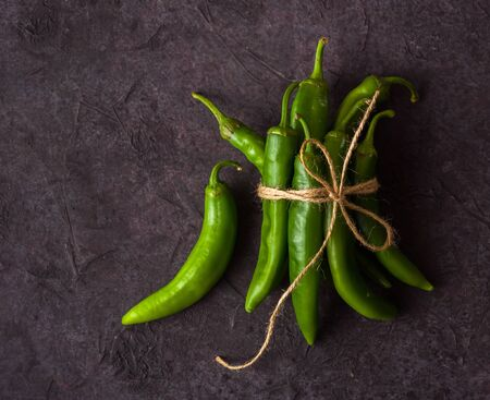 A few green hot peppers shot from above on a dark stone background. Plenty of space for text Stok Fotoğraf - 130136826