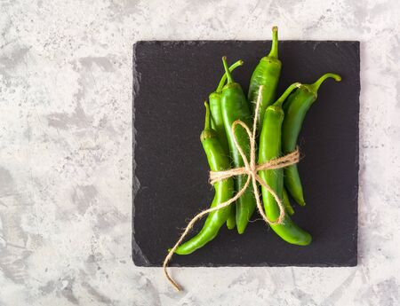 A few green hot peppers shot from above on a light stone background. Plenty of space for text Stockfoto