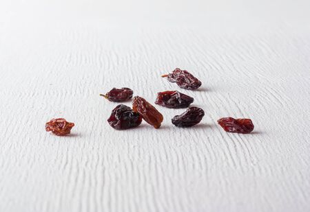 A variety of peeled walnuts and raisins on a white wooden background. View from above. Plenty of space for text Фото со стока - 130136834