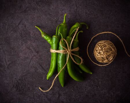 A few green hot peppers shot from above on a dark stone background. Plenty of space for text Stok Fotoğraf - 130136929