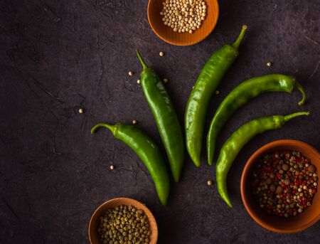 A few green hot peppers shot from above on a dark stone background. Plenty of space for text. Stok Fotoğraf - 130136937