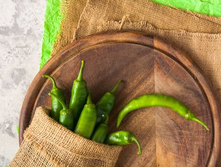 A few green hot peppers in a pouch shot from above on a light stone background and cutting board. Plenty of space for text. Stok Fotoğraf - 130136950