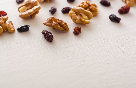 A variety of peeled walnuts and raisins on a white wooden background. View from above. Plenty of space for text. Фото со стока - 130136959