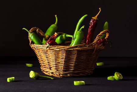 A variety of green hot peppers in a small bucket. Seasoning for a delicious dish.