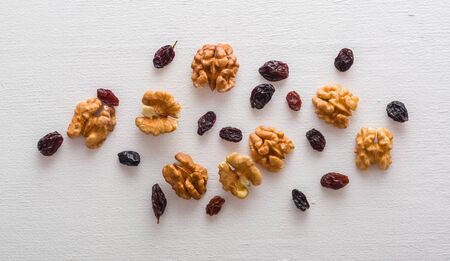 A variety of peeled walnuts and raisins on a white wooden background. View from above. Plenty of space for text. Фото со стока - 130137018