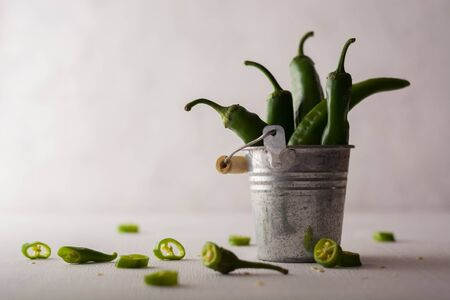 A variety of green hot peppers in a small bucket. Seasoning for a delicious dish. Stok Fotoğraf - 130137022