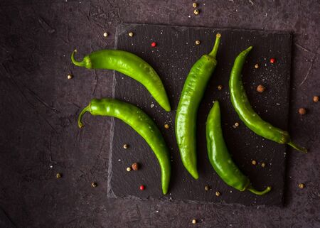 A few green hot peppers shot from above on a dark stone background. Plenty of space for text.