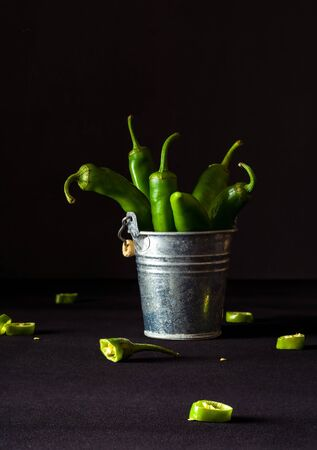 A variety of green hot peppers in a small can. Seasoning for a delicious dish. Stok Fotoğraf - 130137029