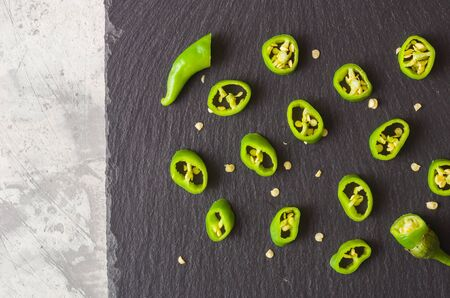 Chopped green pepper spread out on a dark stone background. View from above. For a menu or to advertise a restaurant or cafe.