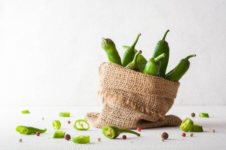 A variety of green hot peppers in a small bag. Seasoning for a delicious dish. Copy space. Zdjęcie Seryjne