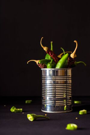 A variety of green hot peppers in a small can. Seasoning for a delicious dish. Zdjęcie Seryjne