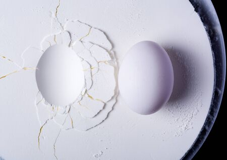 An egg lying on white plaster or starch. Cracks and surface texture. The texture of white gypsum with a microrelief of different shapes. White or light gray kitchen background Stock fotó